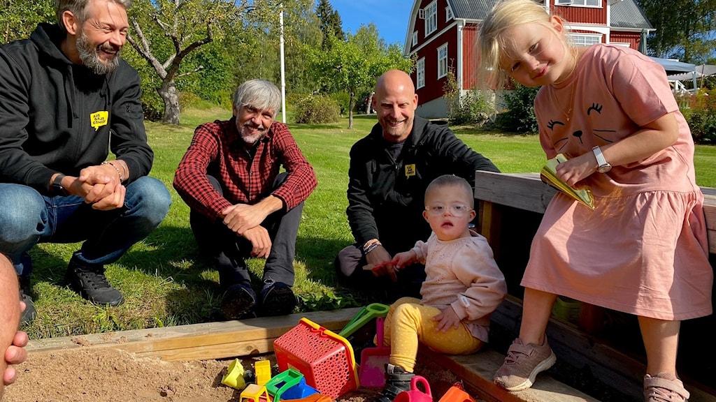 Rickard Wallin (före detta ishockeyspelare), Tobias Östlund (musiker i bandet Broken Door), Andreas Janliden (jobbar med Ajabajacancer) samt barnen Inez och Thea sitter vid en sandlåda.