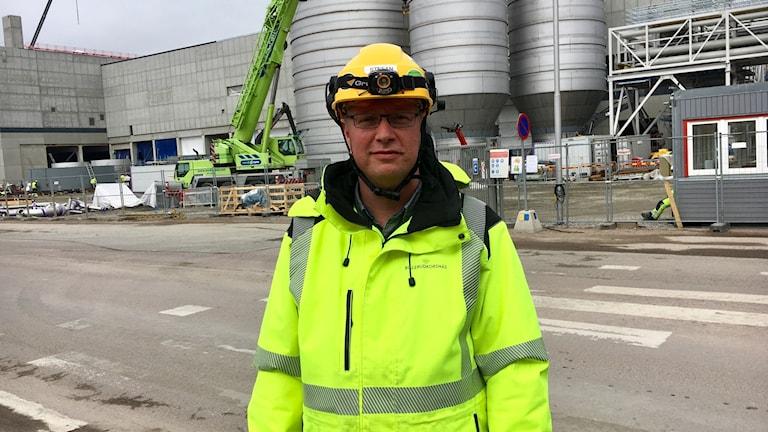 Stefan Holmgren jobbar som är risk och säkerhetschef på Billerud Krosnäs. Här står han i sin varseljacka och arbetshjälm framför bygget på Gruvön i Grums.