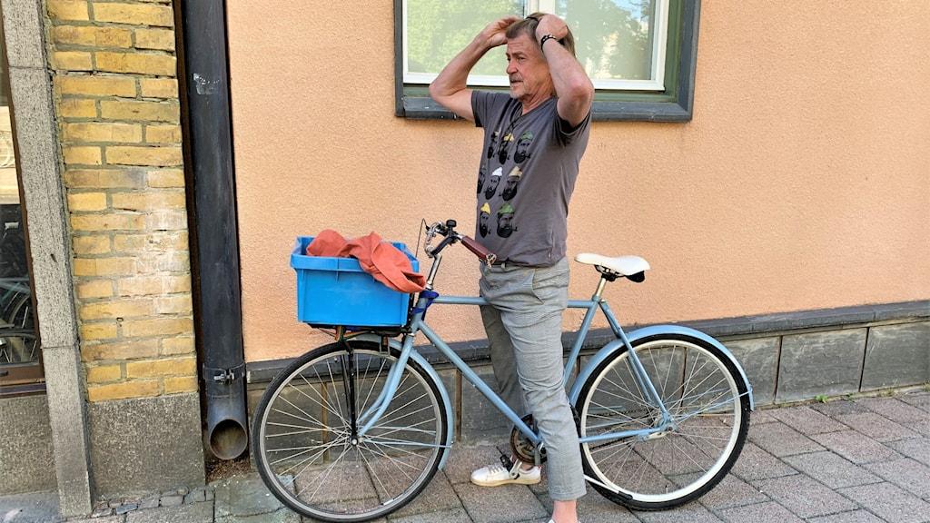 Man på en cykel bredvid en vägg.