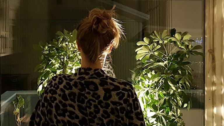 Tjej med blond knut ser ut genom fönster