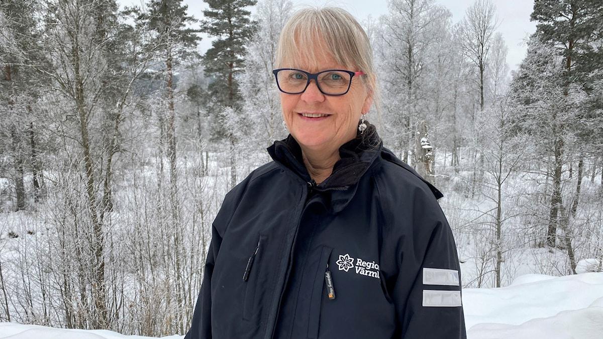 Kvinna med glasögon, vinterlandskap i bakgrunden. Foto: Aron Eriksson