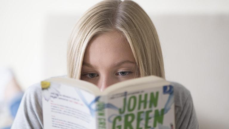 En flicka läser en pocketbok