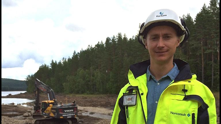 Axel Emanuelsson med en grävskopa som river dammen i bakgrunden. Foto: Veronica Lindström/Sveriges Radio
