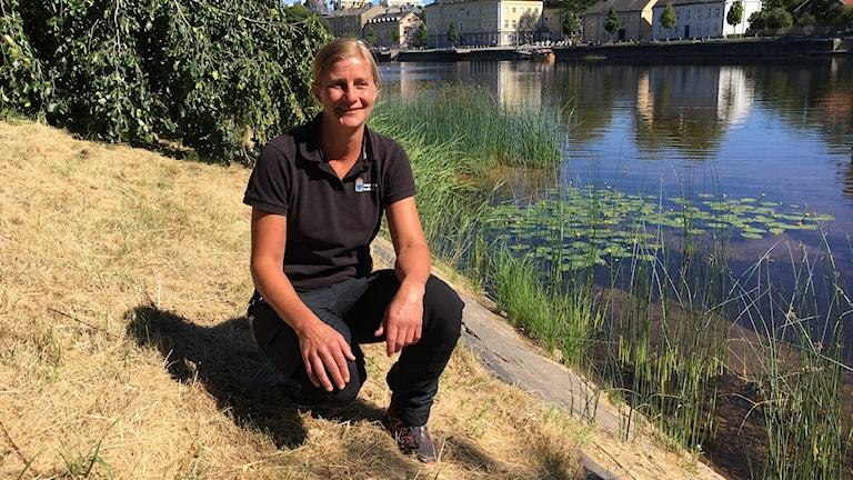 Jenny Monsén biolog vid Länstyrelsen i Värmland sitter på huk vid Klarälvens strand