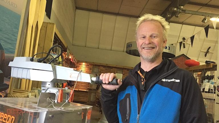 Anders Lindqvist vid en eldriven båtmotor. Foto: Robert Ojala/Sveriges Radio.