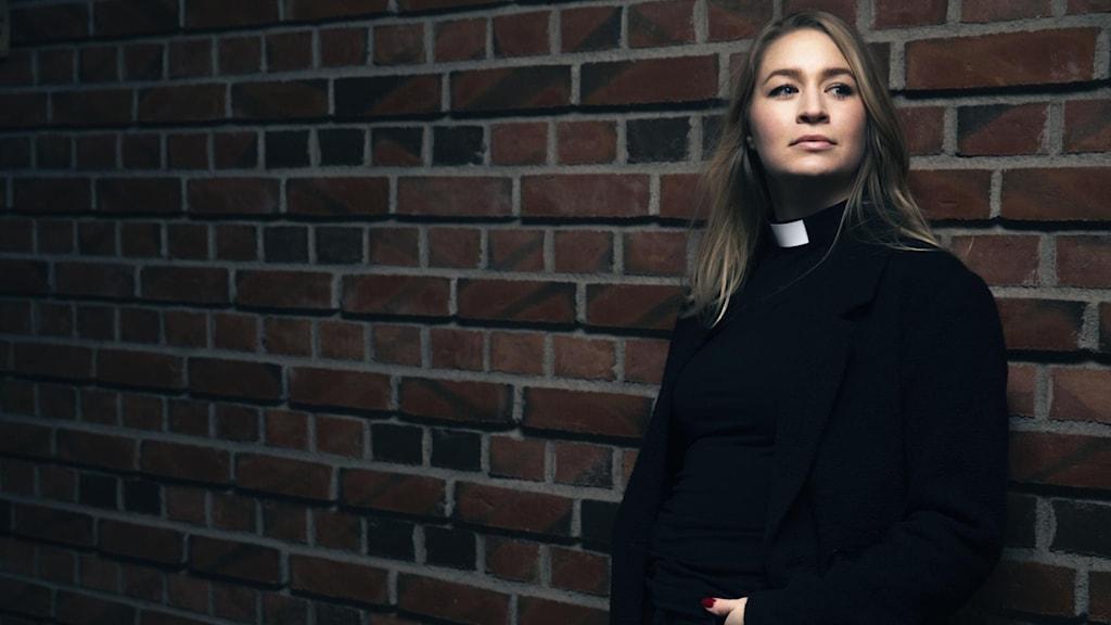 Kvinnlig pastor mot tegelvägg