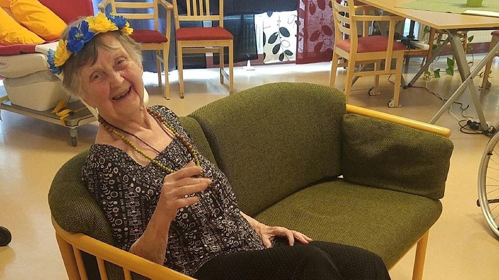 äldre kvinna med blomsterkrans sitter i soffa