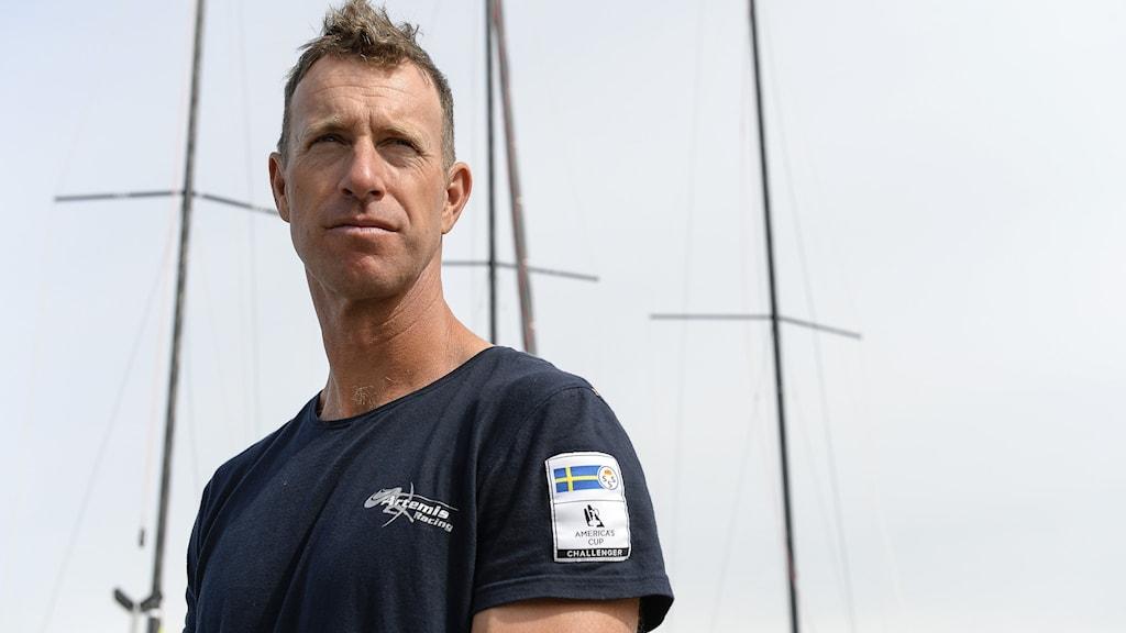 En man står med ett segel på en båt i bakgrunden.