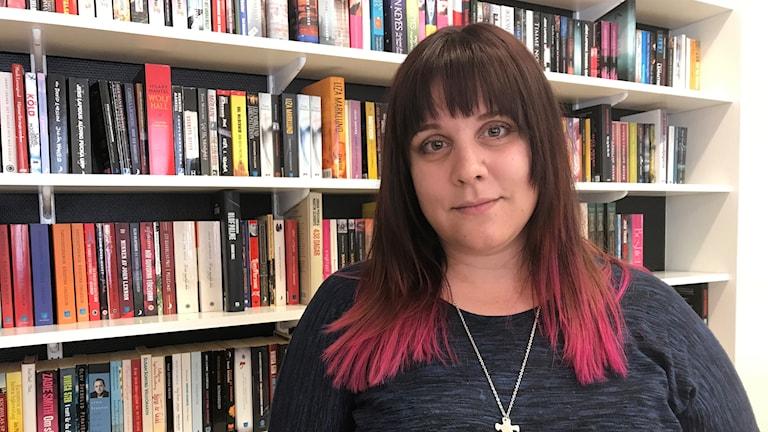 Linda Karlsson syns framför en bokhylla. Hon har brunt hår.