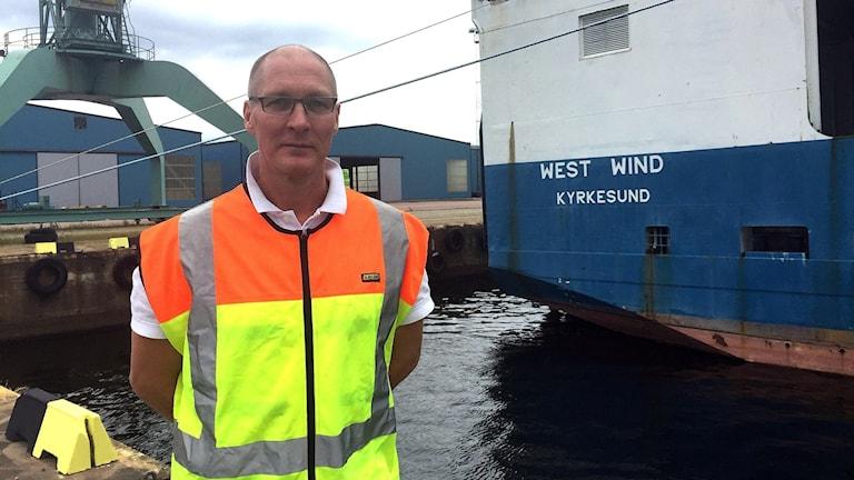 Man står framför aktern på ett lastfartyg i hamnen i Karlstad. I bakgrunden syns också nederdelen av en lyftkran.