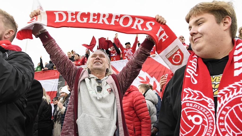 Supportrar som håller upp en halsduk som det står Degerfors IF på.