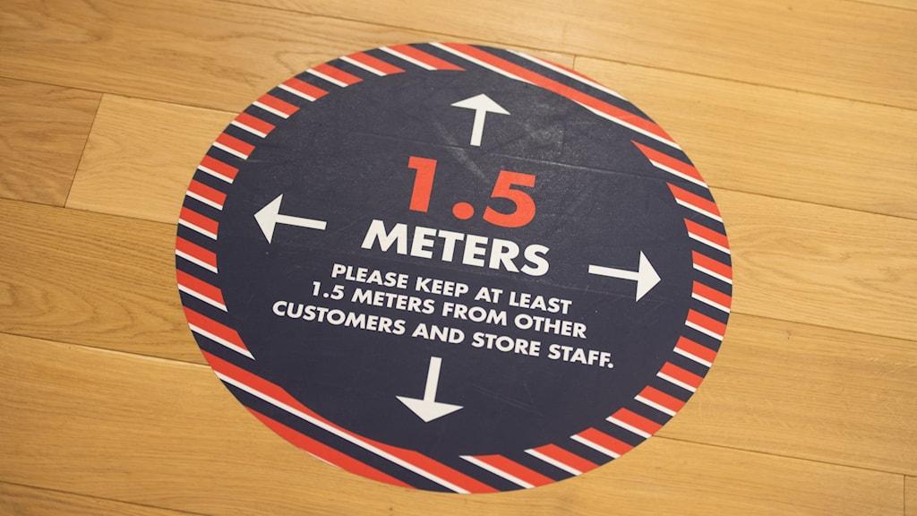Klistermärke på golvet som uppmanar folk att hålla avstånd.