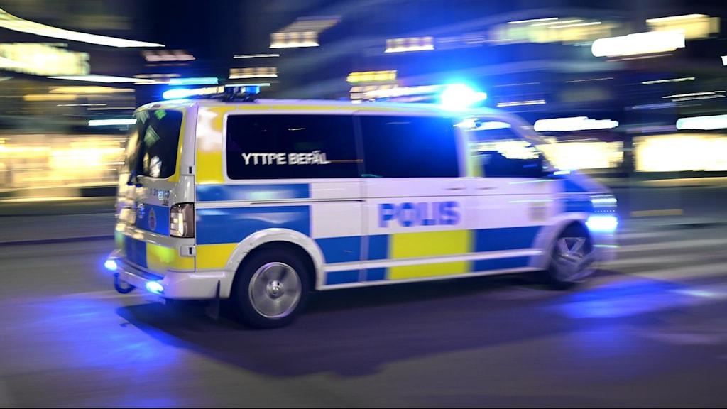 En polisbil kör på en gata.