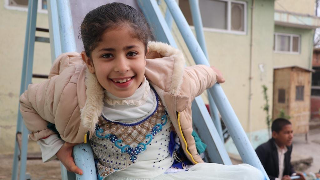 En flicka leker i en rutschkana.