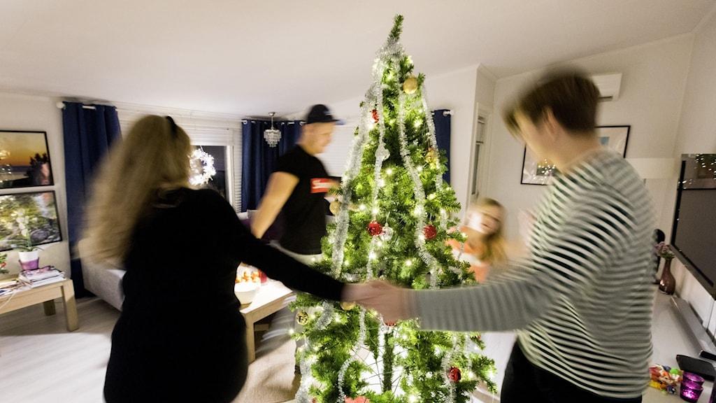 Fyra personer dansar runt en julgran. Foto: Gorm Kallestad / NTB scanpix / TT.