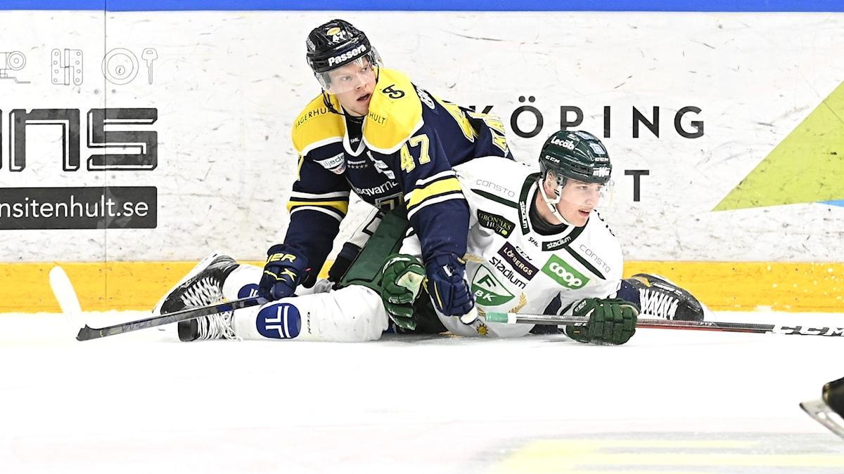 Två spelare som ligger på isen i en hockeyrinkg. Foto: Mikael Fritzon/TT.