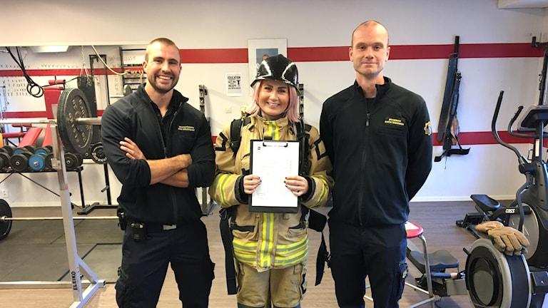 Två brandmän och en brandmansklädd reporter i gymmet.