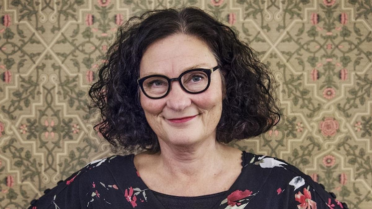 kvinna med glasögon och mörkt lockigt hår