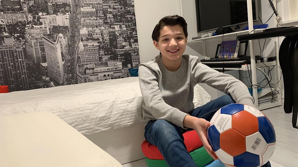 Anastassis Tsiolis, deltagare i Wild kids, sitter i ett vitt rum och håller i en fotboll. Foto: Jonas Berglund/Sveriges Radio.