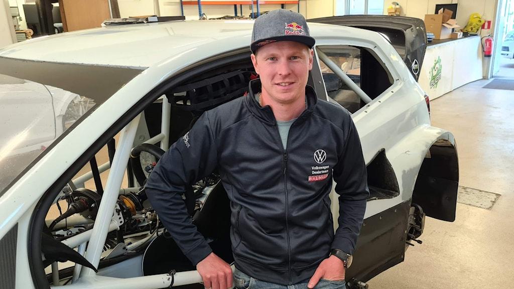 Man i mörk jacka och keps står lutad mot rallycrossbil. Foto: Volkswagen Dealerteam BAUHAUS