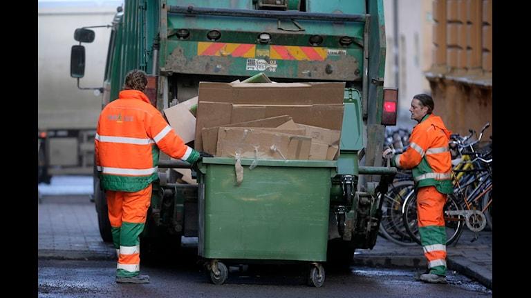 Två renhållningsarbetare tömmer soptunnor i en sopbil. Foto: Fredrik Sandberg/SCANPIX