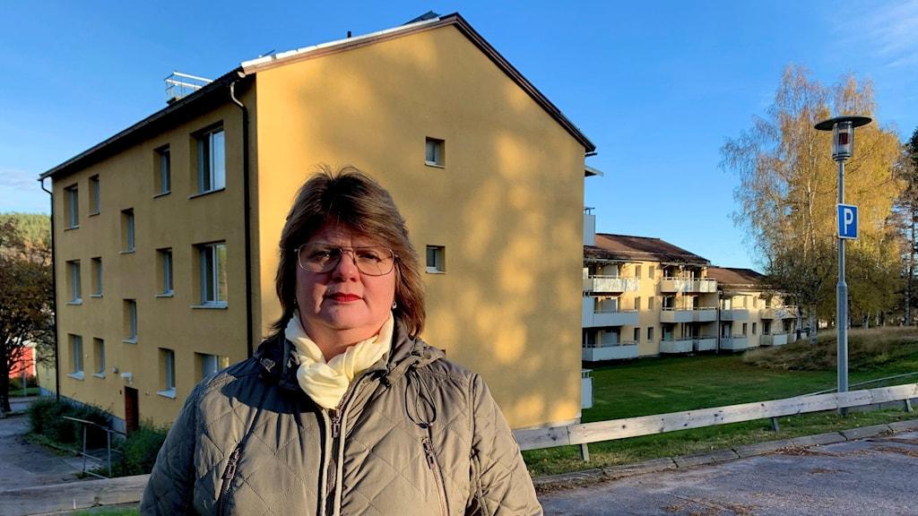 Kvinna står i vinterjack framför de hus i Lesjöfors som ska rivas.