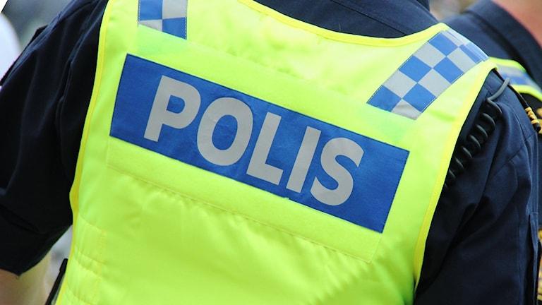 """En polisman i gul väst med texten """"polis"""""""