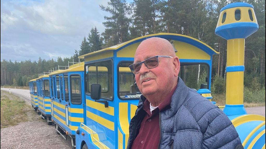 man i glasögon ståendes framför ett turisttåg.