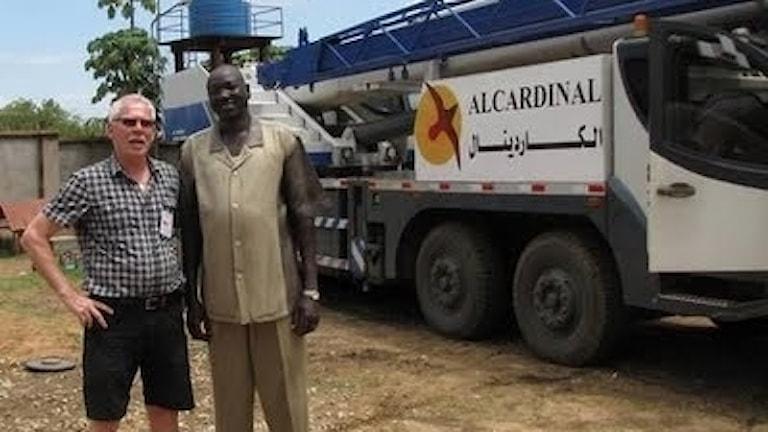 Två män, en vit och en svart, framför en lastbil