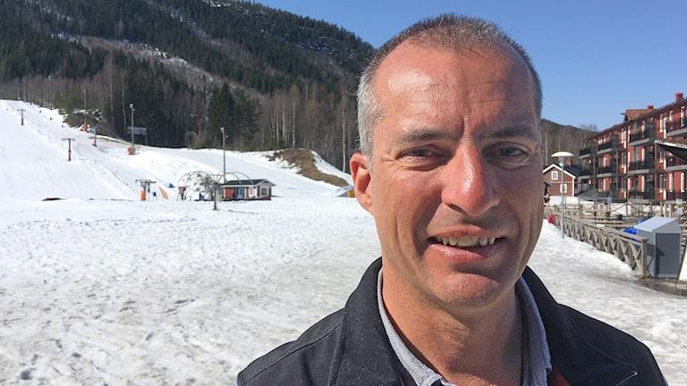 Martin Sturmhoefel med en skidbacke i bag´kgrunden. Foto: Per Larsson/Sveriges Radio.