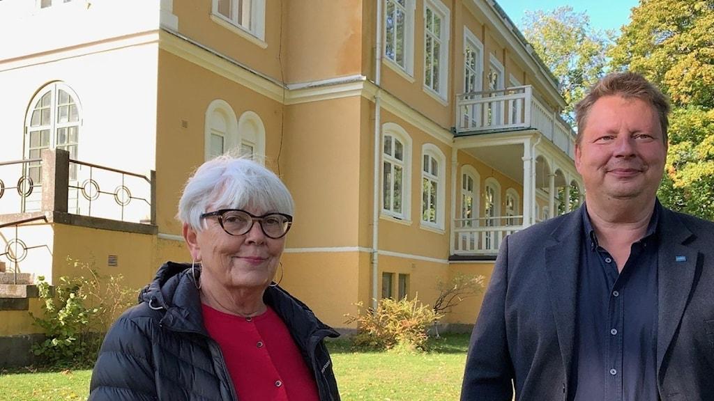 En kvinna och en man står framför ett gult äldre hus. Foto: Tomas Hedman/ Sveriges Radio.