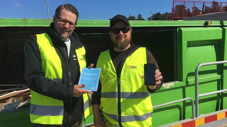 Marcus Edenberg, planeringsingenjör Karlstads energi och P-O Olsson som jobbar på Våxnäs återvinningscentral står i reflexvästar framför en grön container. Foto: Jonas Berglund/Sveriges Radio.