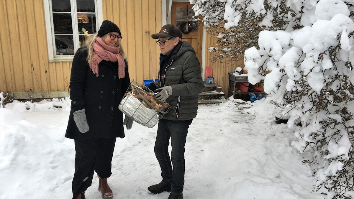 Sofia och Åke Westberg står framför en gul stuga, vid en snöig buske. Foto: Magnus Hermansson/Sveriges Radio.