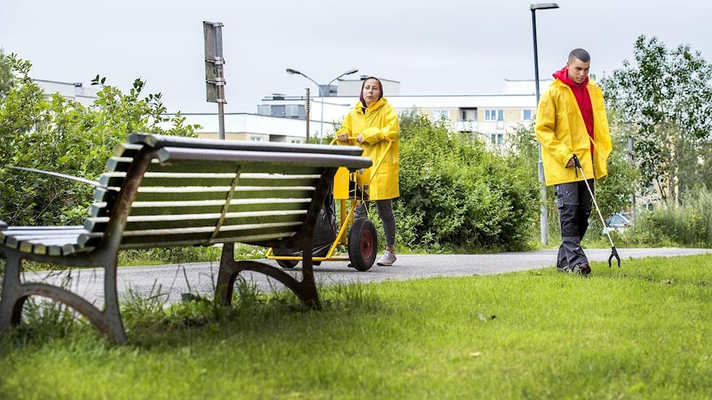 två personer plockar skräp utomhus vid gräsmatta