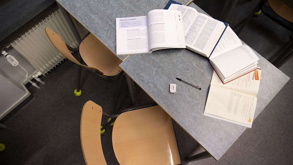 en skolbänk med skolböcker utspridda