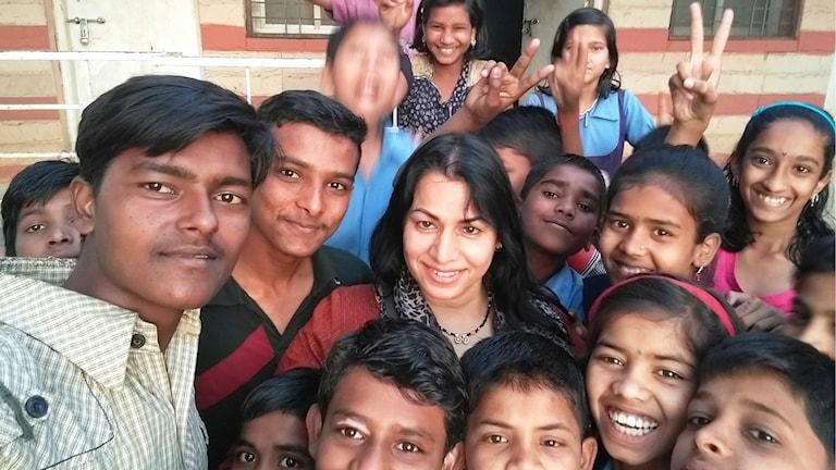 Sarita Skagnes omgiven av många glada barn. Foto:Privat