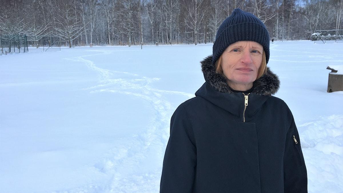 Karin Karlsson, verksamhetschef på Karlstads kommuns kultur- och fritidsförvaltning, står vid snötäckt mark. I bakgrunden skymtar ett skogsparti. Foto: Magnus Hermansson/Sveriges Radio.