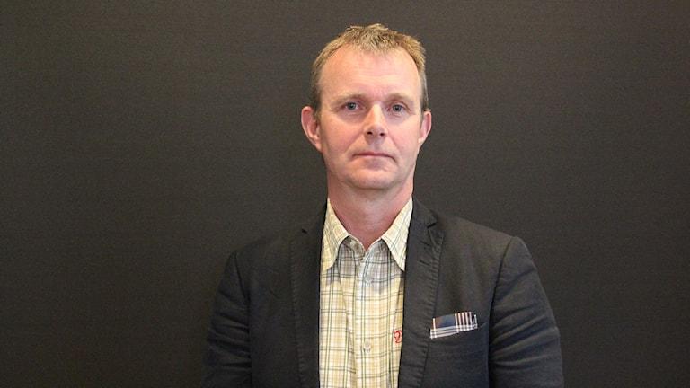 En man i rutigskjorta och svart kavaj står framför en svart vägg.