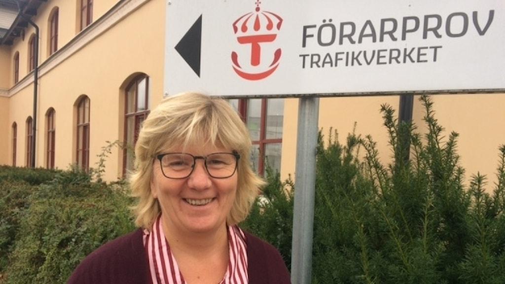 Ann-Christine Juhl framför en skylt där det står förarprov. Foto: Naimi Lundegård/SR
