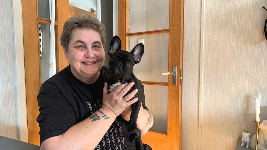 Lone Schyberg med en svart hund i famnen framför en öppen dörr inomhus. Foto: Jonas Berglund/Sveriges Radio.