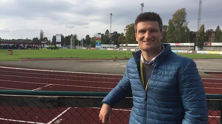 En man står lutad mot ett staket runt en idrottsanläggning som syns i bakgrunden.