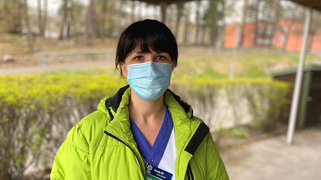 Undersköterskan Annelie Henriksson i gul jacka och munskydd framför en häck. Foto: Jonathan Borg/Sveriges Radio.
