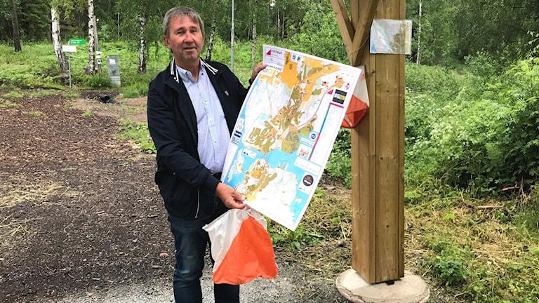 Rhune Magnusson håller i en karta och en orienteringsskärm. Foto: Veronika Svärd Karlsson/Sveriges Radio.