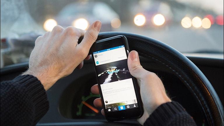 En person håller i en mobil i en bil. Foto: Erik Nylander/TT.