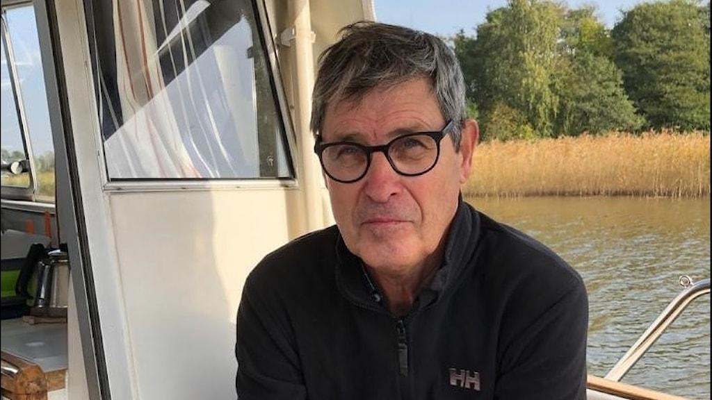 man i glasögon sittandes i en båt.