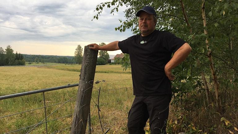 Johan Sandström står framför ett elstängsel. Foto: Gustav Jacobson/Sverigesradio