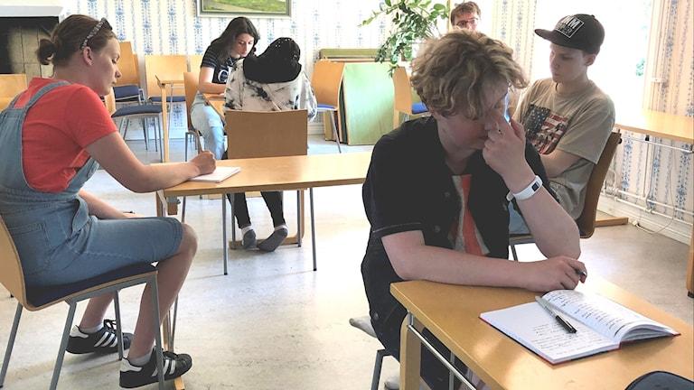 Barn som sitter och läser och skriver.