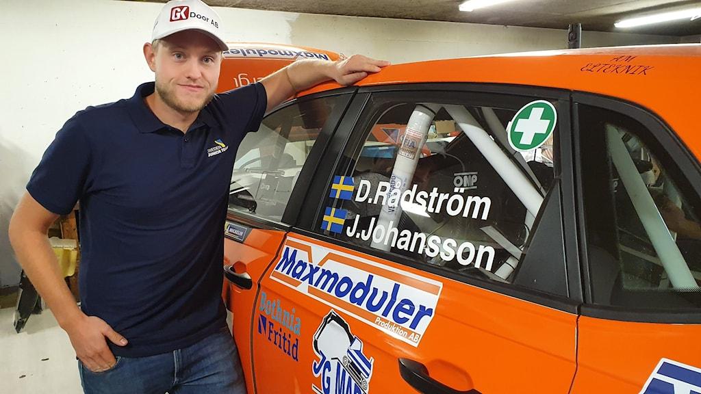 Man stående med ena armen vilande på en orange rallybil. Foto: Aron Eriksson/Sveriges Radio.