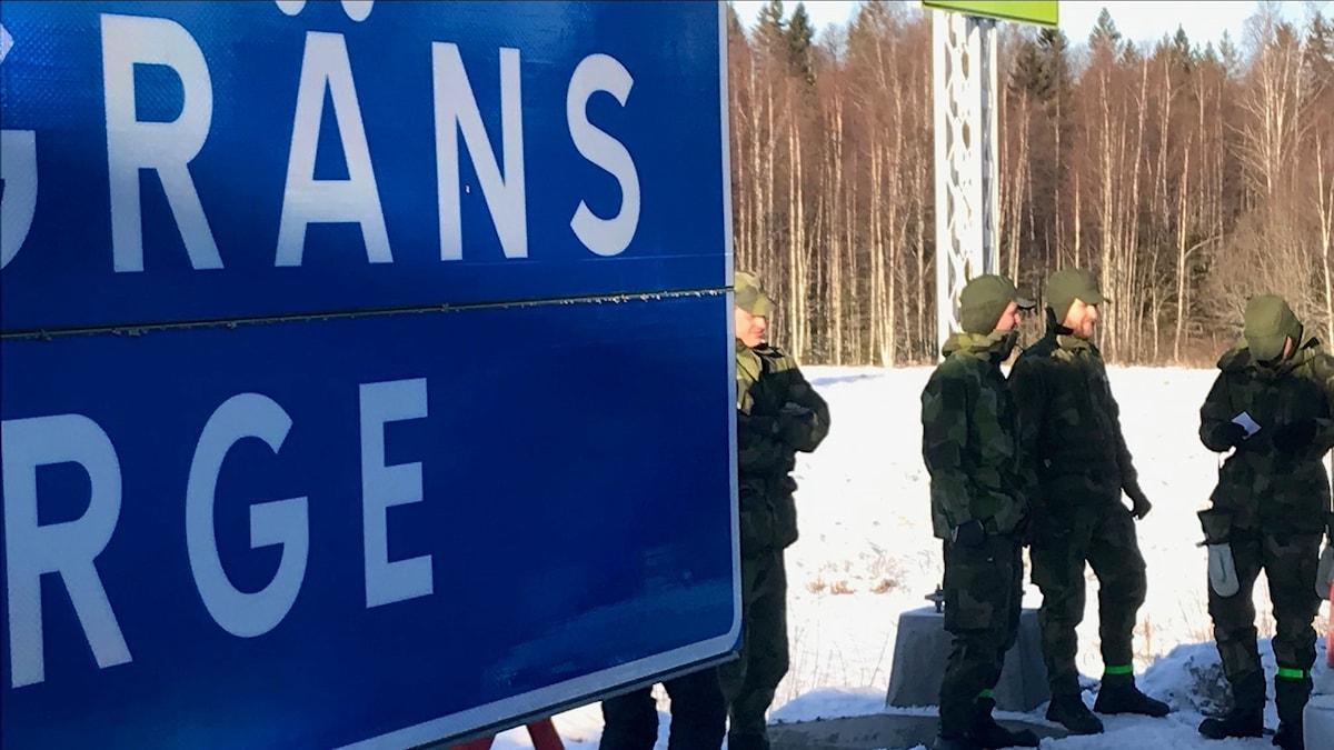 Gränsskylt mot Norge och militärer.