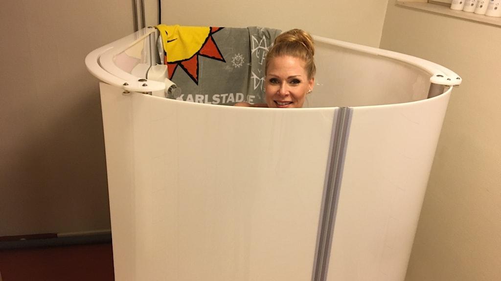 Blond kvinna i dusch med väggar